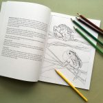 Illustrated book open with text, image and crayons