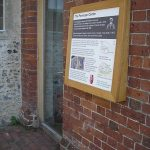 Door with step-free threshold with tactile and clear print interpretive panel