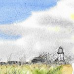 A cloudy sky and wild grass setting for the lighthouse