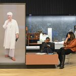 Display panel with Alice looking thoughtfully forward, visitors listen to the audio with headsets